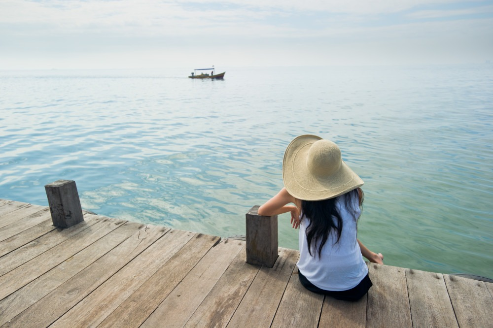 Young Lady With A Hat Sitting On A Pier