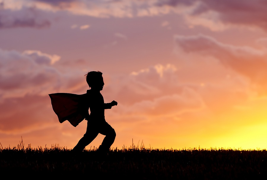 Being your own hero. Silhouette Of A young boy wearing a cape plays a super hero at sunset.