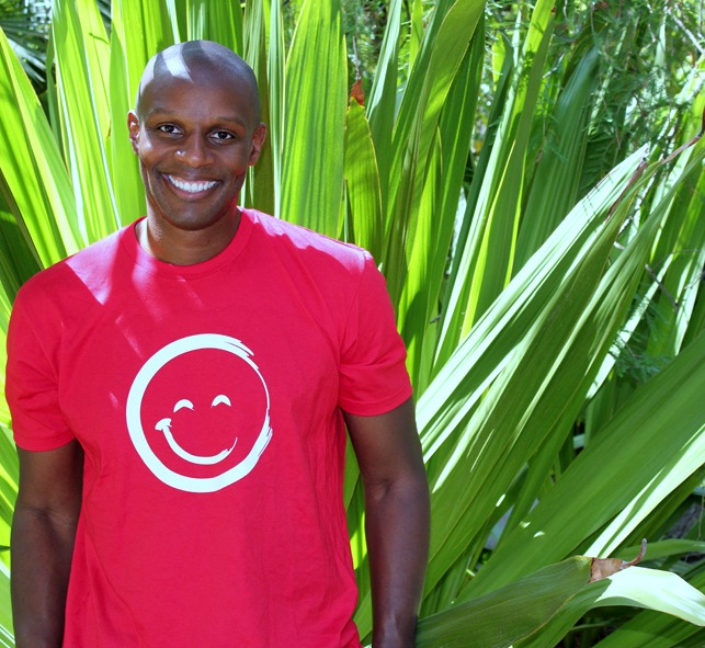 Richard Shola Smiling And Wearing a Red Smiley Face T-Shirt While Standing In Front of Large Plant