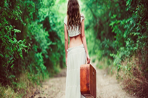 Young Woman With Suitcase in Hand Going Away On A Rural Road