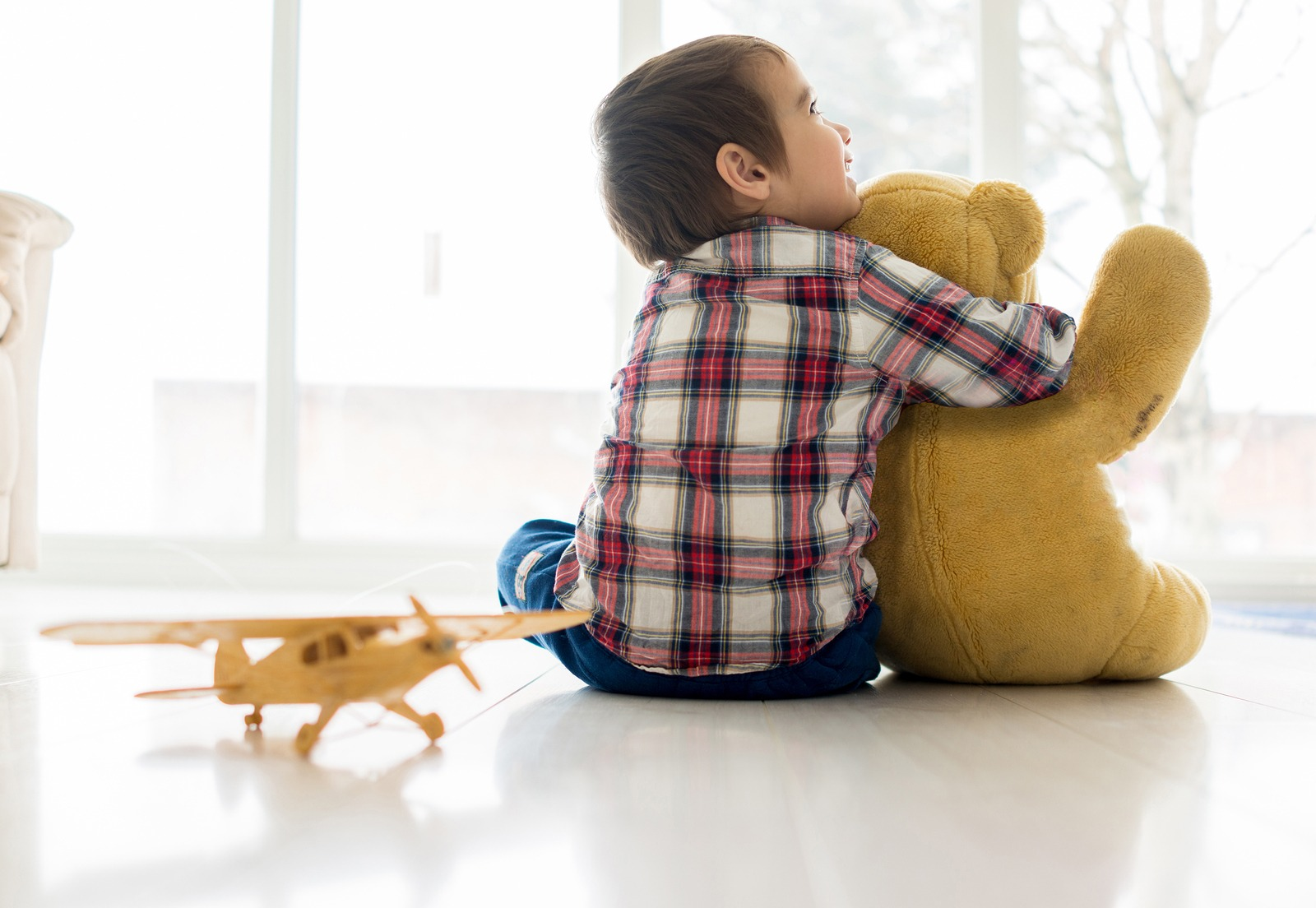 Child sitting in living room with Teddy bear