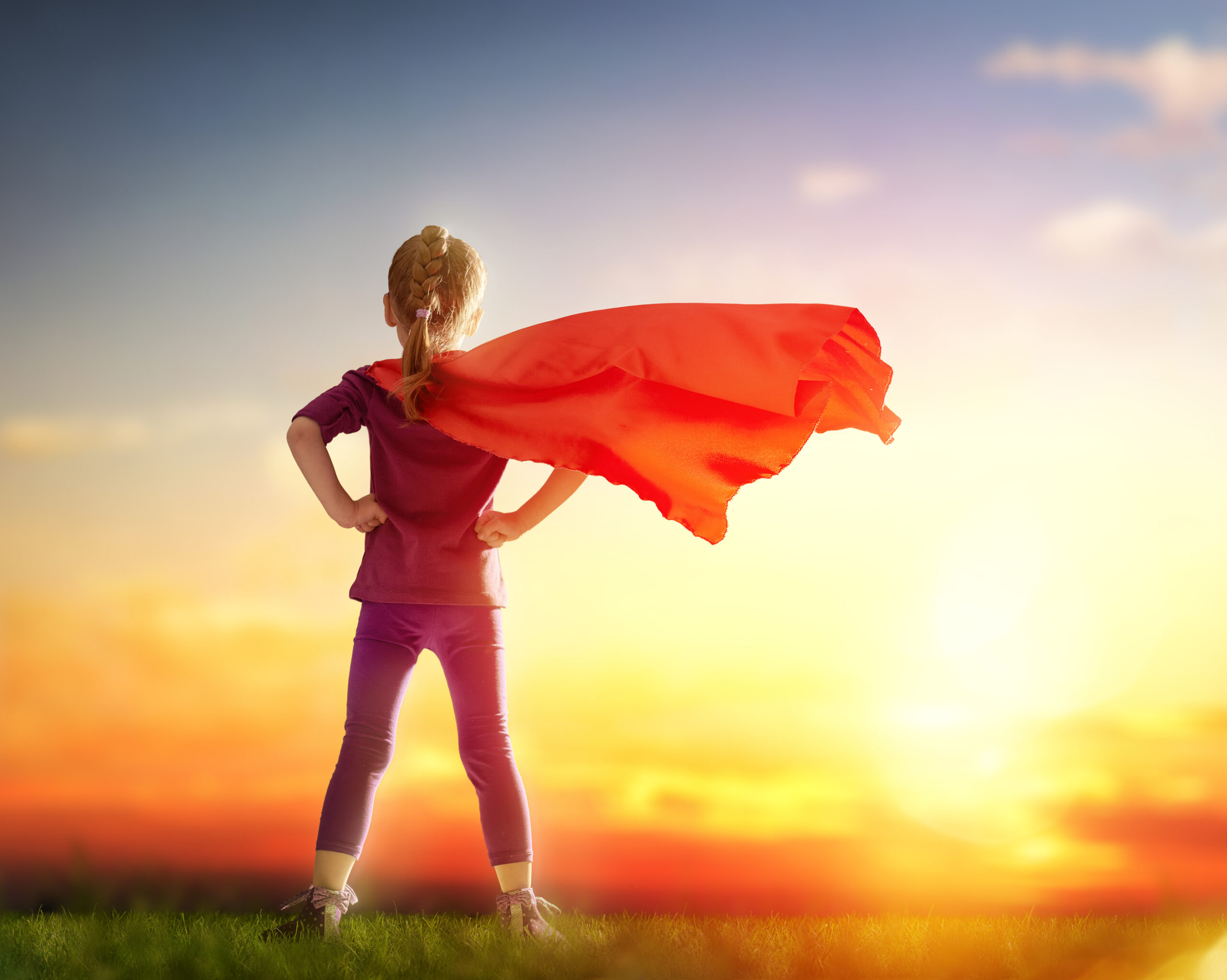 Little child girl plays superhero. Child standing before sunset