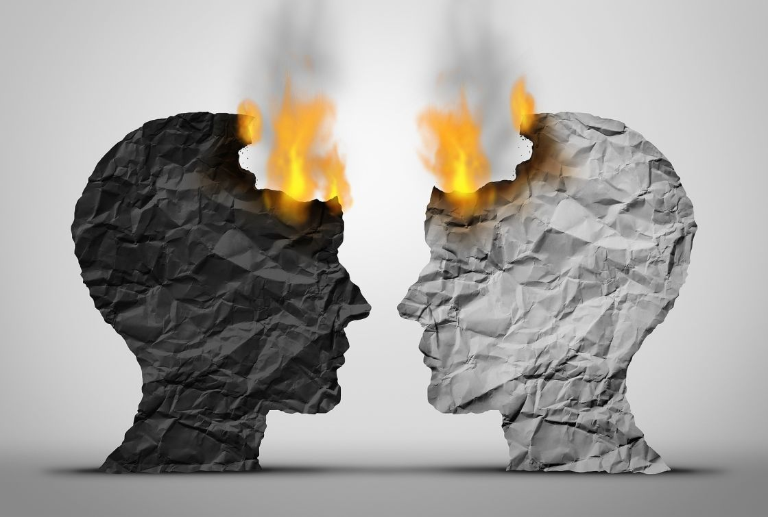 Profiles of Two Faces Made From Paper, One Black and One White, Facing Each Other and Beginning to Catch on Fire