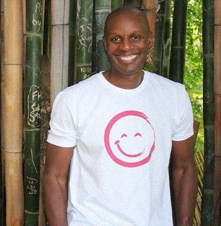 Richard Shola Smiling And Wearing a Smiley Face T-Shirt While Standing In Front of Bamboo