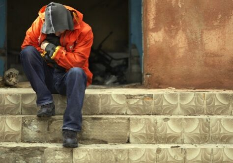 Man in Hoodie With Head Bowed Down Sitting on Top of Steps In Front of Abandoned Building