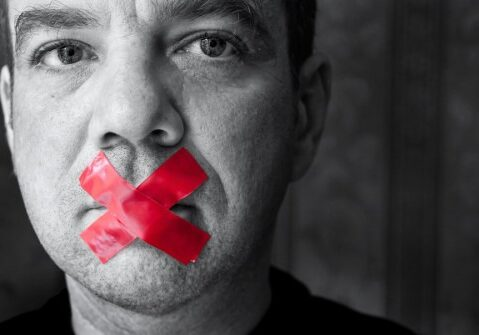 "Man in Black and White With Red Tape in an ""X"" Over His Mouth"