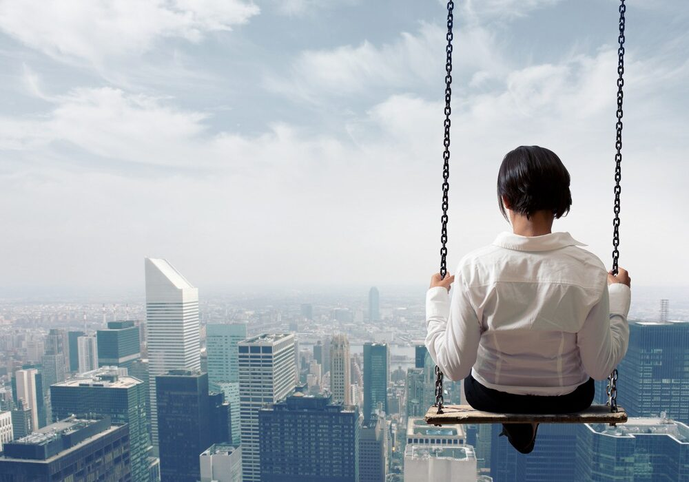 Young Businesswoman Sitting On A Swing Over a Cityscape
